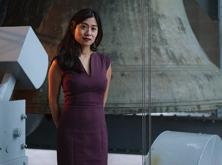 Photo of Tiffany Ng in front of a carillon bell