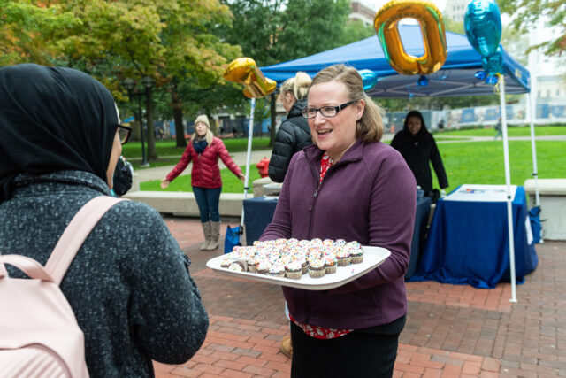 Lindsey Sorgenfrei, assistant director of conference and event services, hands out cupcakes on the Diag as part of 100th birthday celebration for the Michigan Union