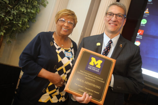 Photo of Laurita Thomas, former associate vice president for human resources, presenting the 2019 James T. Neubacher Award to North Star Reach CEO Doug Armstrong at a ceremony Oct. 25.