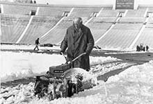 Fritz Crisler helps clear snow from the field of Michigan Stadium in 1966.