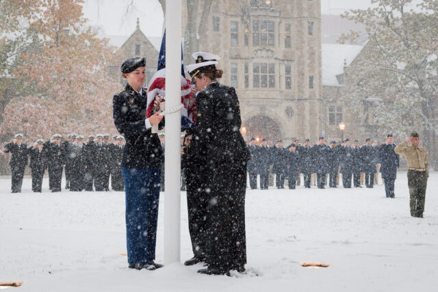 Photo of Army Cadet Catherine Groenke, and Midshipmen Derek Miller and Halle Hassett raising the American flag on the Law Quad