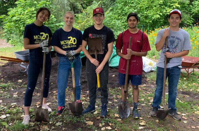 From left, Sarah Ong, Jordan Manley, Vincent Sposato, Rahul Ribiero and Josh Salenbien pose with shovels at the Growing Hope Urban Farm in Ypsilanti. All five U-M students are members of the Michigan Community Scholars Program under the umbrella of LSA. (Photo by Emily Welch)