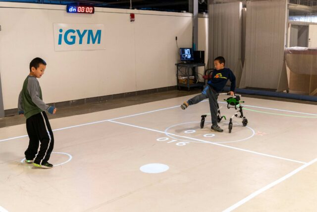 "Darren Kreps (left) and his brother Bryan Kreps participate in a ""play test"" of iGym, an augmented reality system created by a multidisciplinary team at the University of Michigan that promotes inclusive play and exercise."