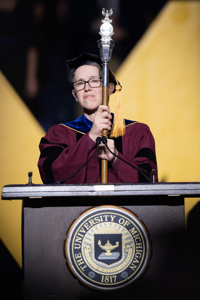 SACUA Chair Joy Beatty presents the university's mace, a symbol authority at U-M ceremonies.