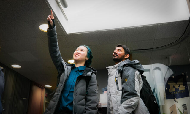 UM-Dearborn College of Engineering and Computer Science graduate students Christine Li (left) and Viraj Tulaskar inspect a skylight in the Administration Building as part of the DTE Energy E-Challenge Competition. (Photo courtesy of UM-Dearborn)