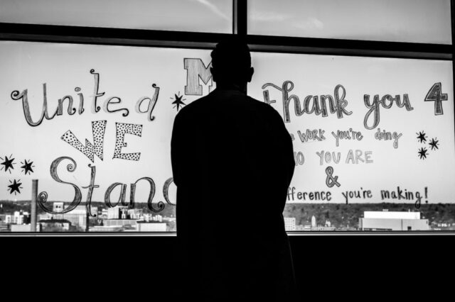 """A Michigan Medicine worker looks at a """"thank you"""" message on a window."""