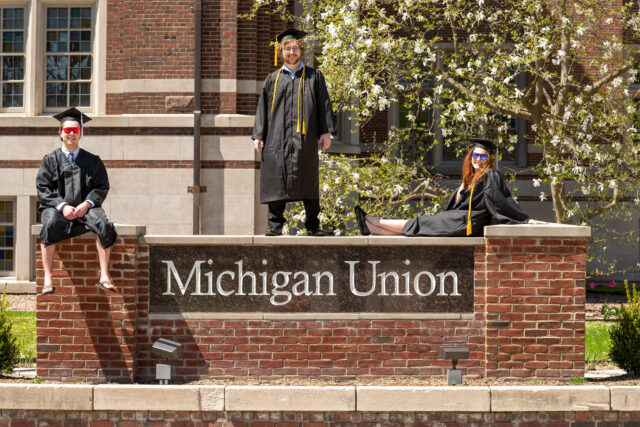 Soon-to-be U-M graduates Conor Donahue, Myles Lovasz, Zoe Solomon, pose on the sign for the Michigan Union on May 1, 2020.