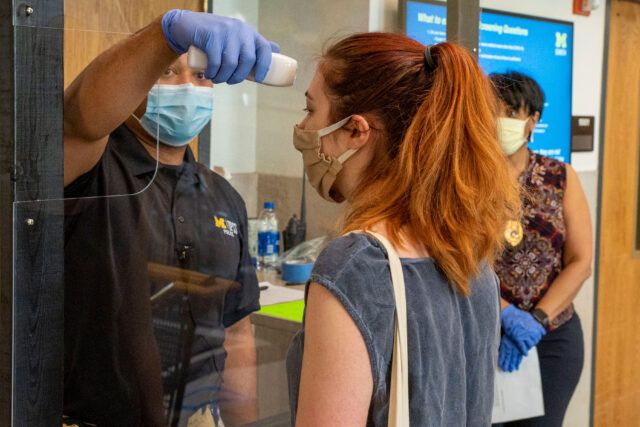 Catherine Polik, a research laboratory technician with LSA's Department of Earth and Environmental Sciences, has her temperature checked by Lt. Akin A. Bryant of the Division of Public Safety and Security before entering the North University Building on May 21.