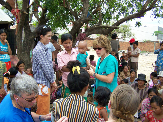 Maureen Tippen, a clinical associate professor emerita of nursing at UM-Flint and this year's recipient of the President's Award for Distinguished Service in International Education, works with members of a Cambodian village during a trip to that country. (Photo by Nicole Richon)