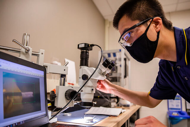 Yi Zhu, graduate student research assistant in civil and environmental engineering, tests a new generation of micro-robotics inside Evgueni Filipov's lab at the G.G. Brown Building on North Campus. (Photo by Robert Coelius, College of Engineering)