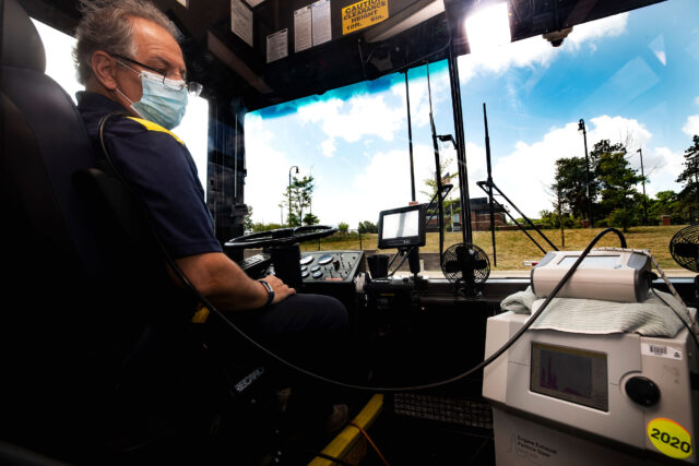Photo of Andre Boehman, professor of mechanical engineering, and members of his research group testing for the flow of aerosols in a U-M bus. (Photo by Joseph Xu, College of Engineering)