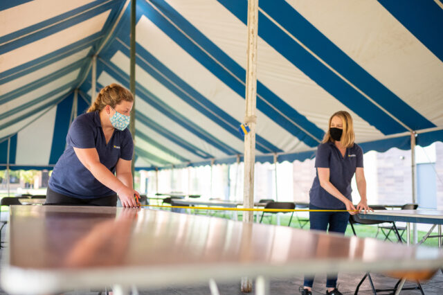 Photo of Jennifer Pomerantz (left) and Elaine Hanke of Michigan Conference & Event Services measuring the distance between tables inside a tent on North Campus.