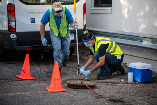 Philip Szornyi and Anthony Shourds of Environment, Health and Safety collect sewage samples behind U-M's Campus Safety Services Building in August, before students began moving into residence halls.  Eric Bronson, Michigan Photography