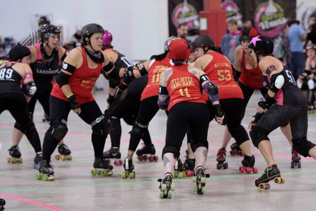 Devon Kinney, third from left, blocks in a Quad County Roller Derby match. Kinney said she prefers blocking to either jamming or being the pivot. (Photo courtesy of Soul Collector/DeFord Designs)