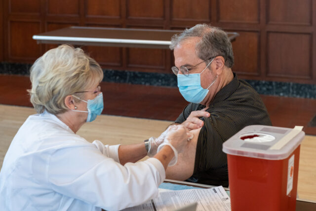 President Mark Schlissel receives his flu shot Sept. 14 from Debbie Renna in the Rogel Ballroom of the Michigan Union. Faculty, staff and students have multiple options to receive a flu shot, which is deemed even more important during the current COVID-19 pandemic.