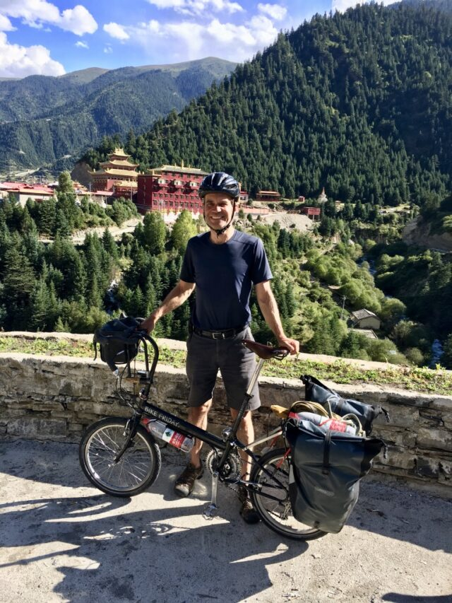 Stefan Koehler poses in summer 2019 in Sichuan Province, China, with a Tibetan monastery in the background. (Photo courtesy of Stefan Koehler)