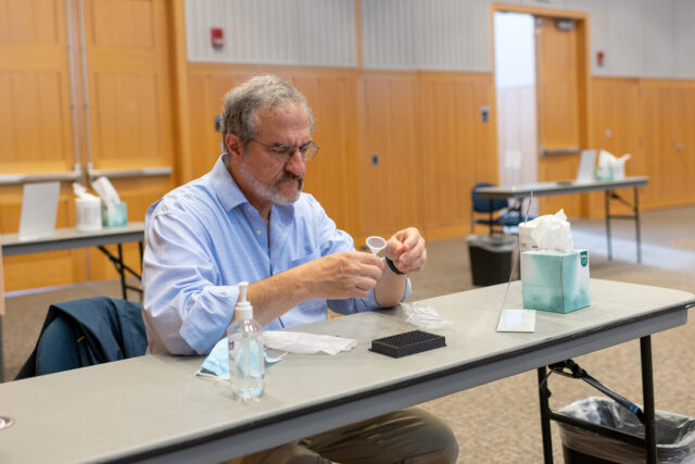 Photo of President Mark Schlissel preparing to take a saliva-based COVID-19 test.
