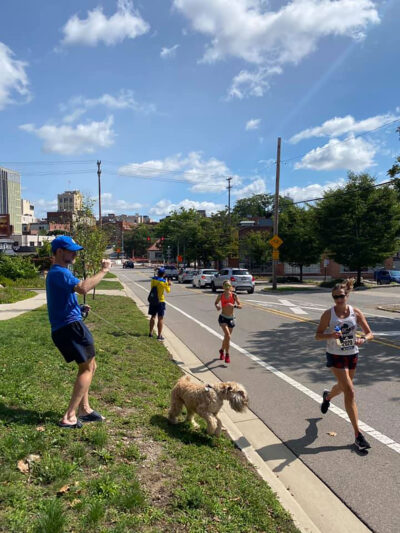 Colleen Stone approaches the finish line of the virtual Boston Marathon in Ann Arbor as her husband, Paul Livingstone, tries to capture a photo while also corralling their dog, Stevie.