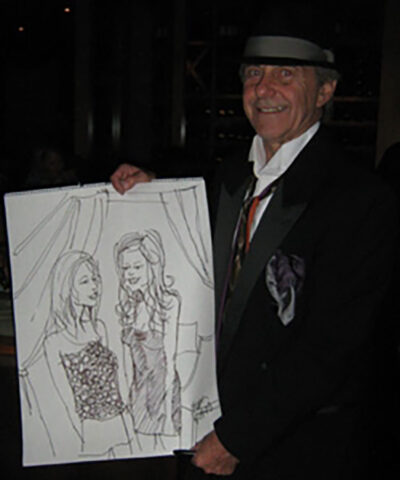 Gary Bohas, a stockkeeper at the U-M Central Power Plant, shows off a portrait he created, one of thousands of drawings of celebrities and strangers he's drawn on paper napkins over the years. (Photo courtesy of Gary Bohas)