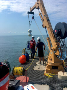 Researchers lower a robotic laboratory to the bottom of Lake Erie's central basin in July 2019 for a U-M-led study of phosphorus released from muddy lake-bottom sediments. Two of the autonomous labs were deployed: one at a depth of 67 feet and the other at a depth of 79 feet. (Photo by Hanna Anderson.)