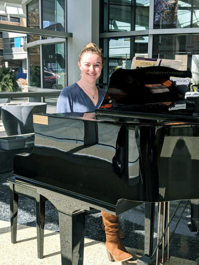 Emily Wheeler, guest services specialist at the Division of Public Safety and Security, sits at the baby grand piano in the lobby of C.S. Mott Children's Hospital. She has spent many days off from her position to play mostly classical tunes for the visitors, patients and staff at the hospital. (Photo by Jacob Baxter)