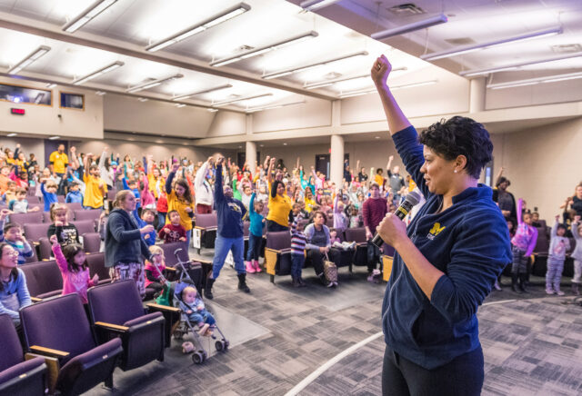 Rebecca Hasson, associate professor of movement science in the School of Kinesiology, leads children and others through song, dance and activities in 2018 during the annual MLK Children and Youth Program, which attracts K-12 student participants from school communities throughout southeastern Michigan. (Photo by Scott C. Soderberg, Michigan Photography)