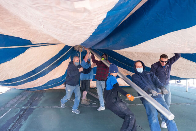 Photo of workers from Delux Tents and Events of Belleville putting up a canopy at the Palmer Tennis Courts