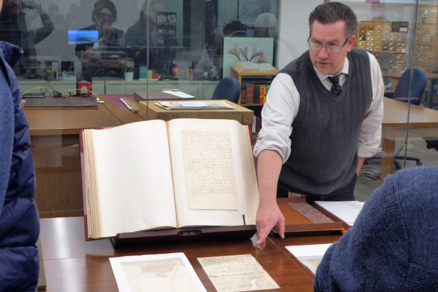 Photo of Cheney Schopieray, curator of manuscripts at the Clements Library, pointing to Thomas Gage's original draft of his order to seize military stores at the town of Concord, west of Boston, April 18, 1775.