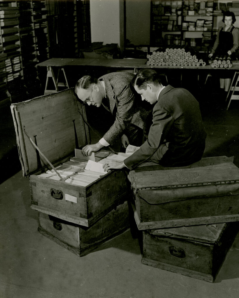 Photo of curators and staff members Lloyd Brown, Howard Peckham and Margaret Webber with four trunks of Thomas Gage papers in 1937.
