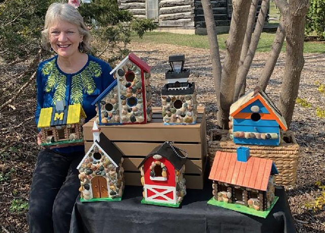 Sally Sivrais, research administrator senior manager at PM&R in the Medical School, poses with several birdhouses she's built, painted and decorated with stones she picked up from Lake Michigan and Lake Superior beaches. (Photo courtesy of Sally Sivrais)