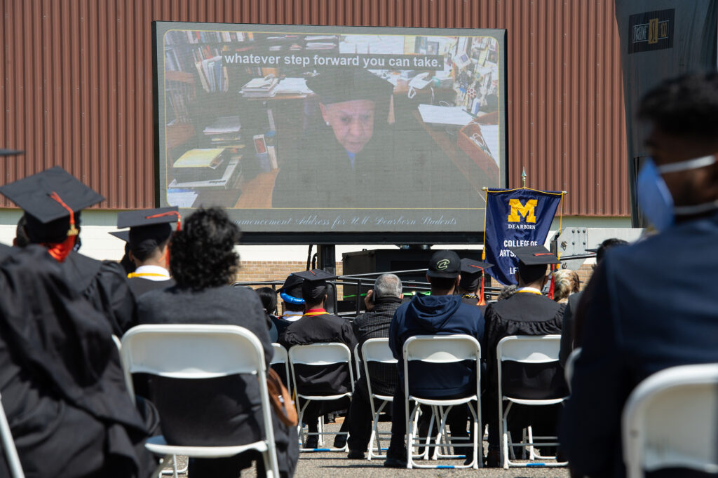 A small audience watches videos of commencement speakers at UM-Dearborn's ceremony for the College of Engineering and Computer Science graduates. (Photo by Austin Thomason, Michigan Photography)