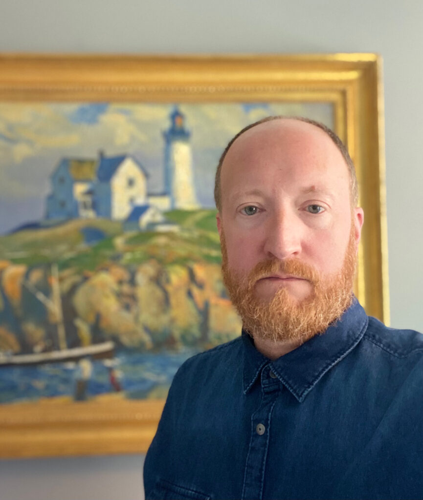 """Darin Leese, a business systems analyst for My LINC through Information and Technology Services, poses in front of """"Nubble Lighthouse,"""" a painting by Clarence Chatterton. (Photo by Darin Leese)"""