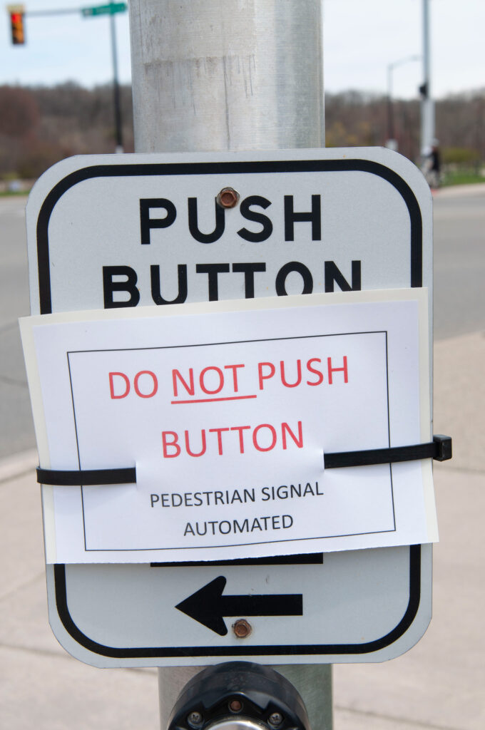 A sign in downtown Ann Arbor warns pedestrians to not push the button. (Photo by Henry Hedly, Michigan Medicine)