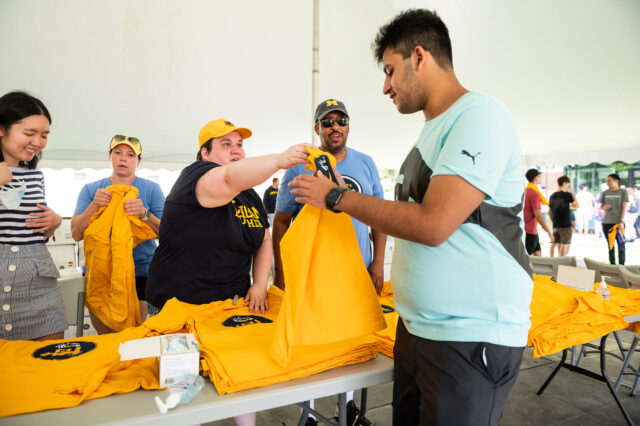 Photo of woman handing a sophomore student a T-shirt.