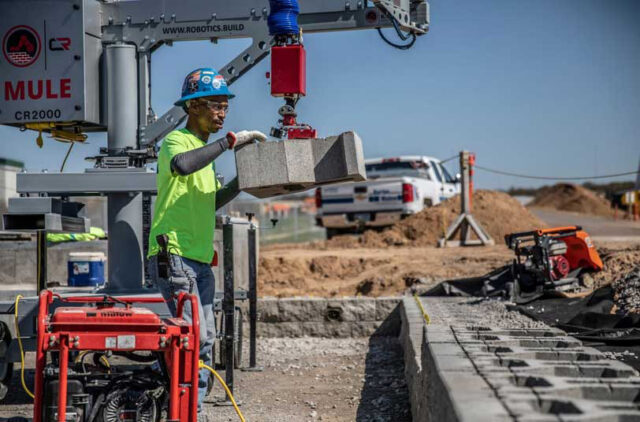 Photo of a construction worker using a robot to place concrete blocks