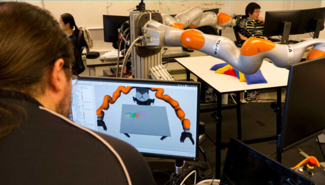 Photo of A U-M graduate student operating a KUKA robot