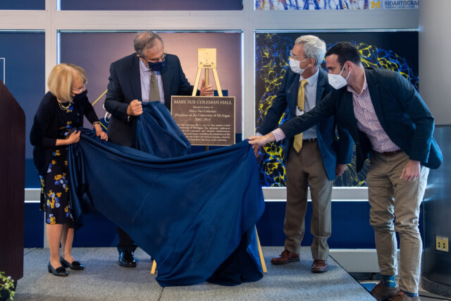 Photo of a plaque being unveiled at the naming of Mary Sue Coleman Hall
