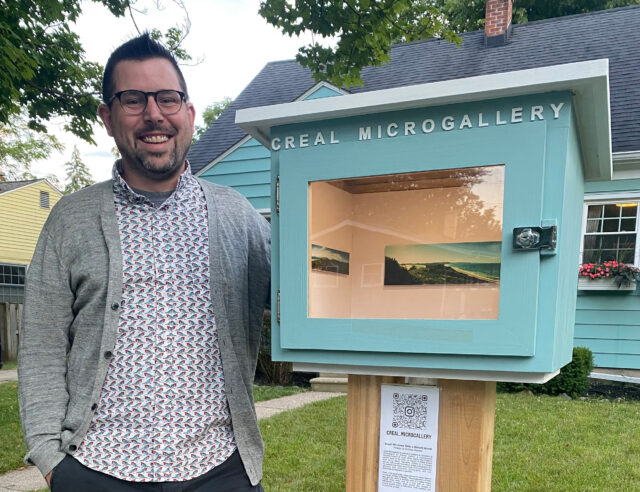 Joe Levickas, program director for Arts at Michigan and assistant director in the Office of New Student Programs, stands next to Creal Microgallery, a small art exhibit space he installed in his front yard. (Photo courtesy of Joe Levickas)