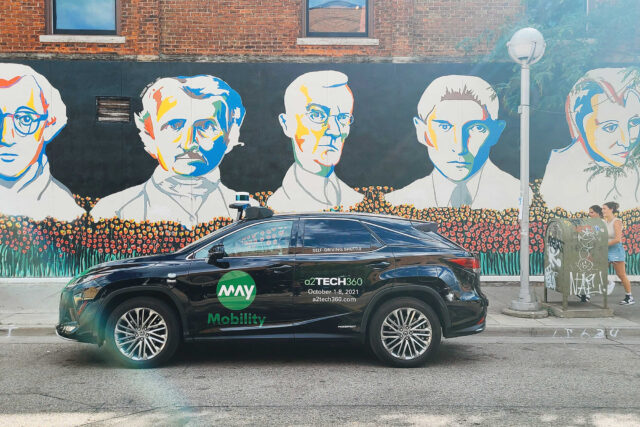 A photo of an A2GO vehicle in front of an iconic downtown mural along Liberty Street.
