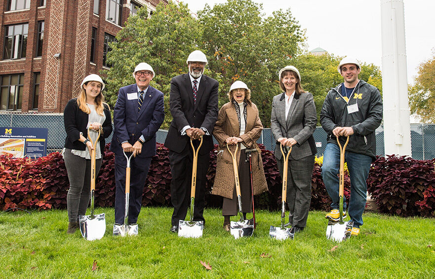 Photo of people digging first shoveful at groundbreaking for Kraus building