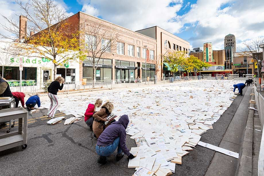 """Photo of volunteers """"paving"""" Liberty Street with books."""