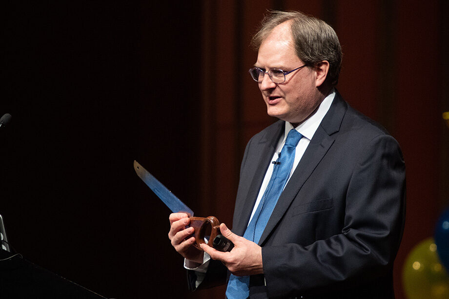 Photo of Mark Conger holding a saw