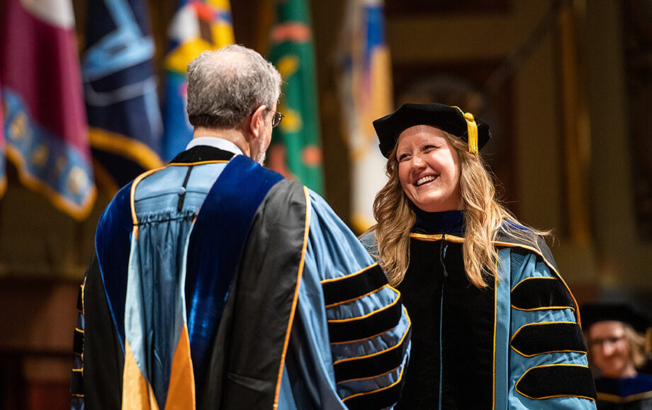 Photo of graduate being congratulated by President Schlissel
