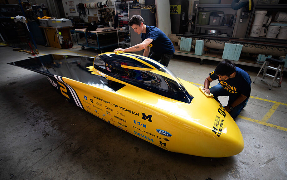 Photo of engineering students Zac Goldsmith, race operations engineer, and Rishabh Goel, race electrical engineer, cleaning the new U-M solar car race vehicle